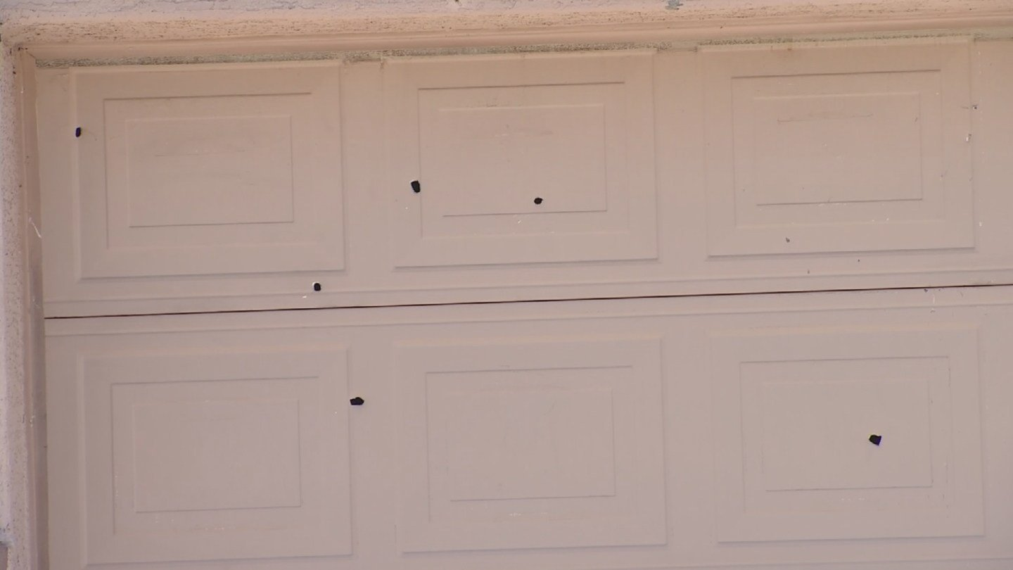 The garage door of the home where the shooting took place is riddle with bullet holes. (Source: 3TV)