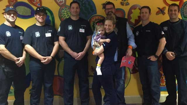 Nineteen-month-old Joy Loboda and her parents pose with crews of Engine and Rescue 17. (Source: Phoenix Fire Department)