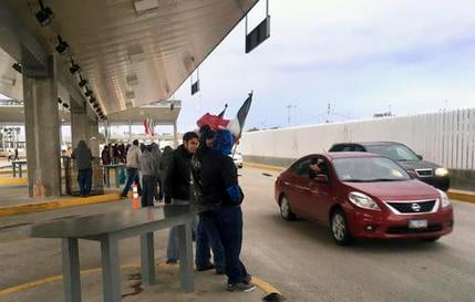 Protesters in Tijuana, Mexico, wave through motorists at the Otay Mesa Port of Entry with San Diego, Calif., after Mexican authorities abandoned their posts on Sunday, Jan. 22, 2017. (AP Photo/Elliot Spagat)