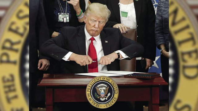 President Donald Trump takes the cap off a pen before signing executive order for immigration actions to build border wall during a visit to the Homeland Security Department on Wednesday. (Source: AP photo)