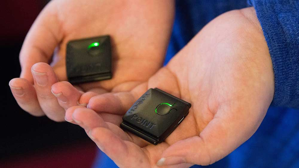 Buzzies display a green light when on and can be held, put into pockets or worn. (Source: Megan Bridgeman/Cronkite News)