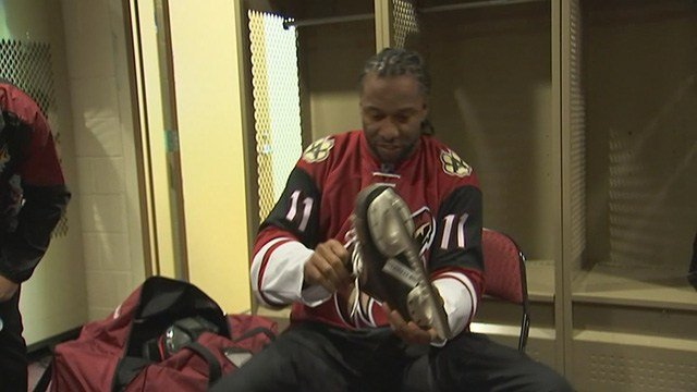 Larry Fitzgerald, in the Arizona Coyotes lockerroom, laces up the ice skates Monday. (Source: 3TV/CBS 5)