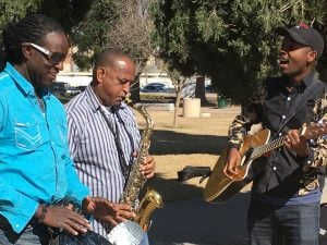Richard Noel, founder of Jam2Grow, drums while Tilahun Liben of Ethiopia plays sax and Jean Marie Menutore of Burundi strums his guitar and sings during a music as therapy session. (Source: Mindy Riesenberg/Cronkite News)