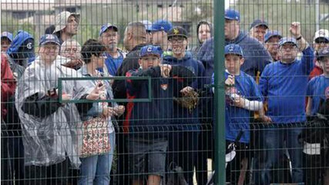 Chicago Cubs fans wait for players outside the team's clubhouse Tuesday, Feb. 14, 2017, in Mesa, Ariz. The team cancelled their workout due to rain in the area. (AP Photo/Morry Gash)