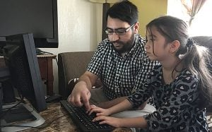 Riad Sbai of PCs for Refugees shows 9-year-old Syrian refugee Aya how to use her family's new computer. (Source: Mindy Riesenberg/Cronkite News)