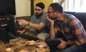 Riad Sbai of PCs for Refugees (left) shows Firas Kharma, a refugee from Syria, how to navigate the Internet with his new computer. (Source: Mindy Riesenberg/Cronkite News)