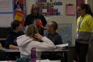 Teacher Heather Robinson hands out less-desirable lollipops to students Caleb Kaufman, Brandon Barnes and Mackenzie Leblanc (seated, left to right) during an exercise to teach her students about segregation. (Source: Kaddie Stephens/Cronkite News)
