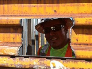 A construction worker peers through the fence at the U.S.-Mexico border in Naco. (Source: Gretchen Baer)