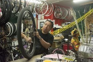 "The Garage Bike Shop owner Rene Pulido fills a tire with air at the shop. A mainstay at the ""mercado"" in the town of Guadalupe, the shop closed at the end of February. (Source: Ryan Santistevan/Cronkite News)"
