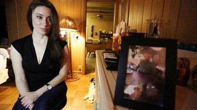 In this Feb. 13, 2017 photo, Casey Anthony poses for a portrait next to a photo of her daughter, Caylee, in her West Palm Beach, Fla., bedroom. (Source: AP Photo/Joshua Replogle)