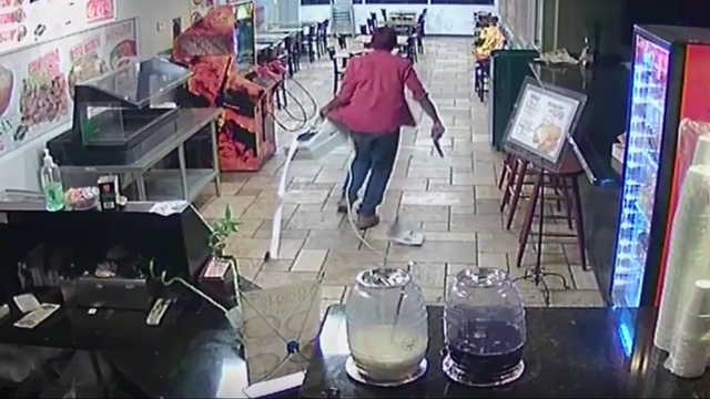 Surveillance video shows suspect running from Armando's Mexican Food Restaurant with the cash register. (Source: Silent Witness)