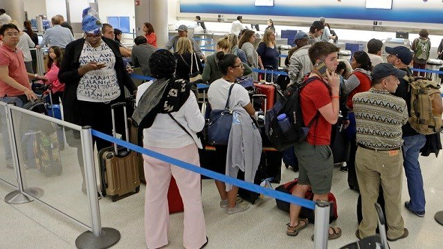 Airline passengers stand in line as they wait to rebook their canceled flights as a winter storm heads toward the Northeast. (AP Photo/Alan Diaz)