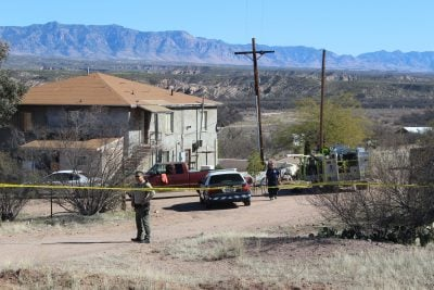 Pinal County sheriff's deputies, Mammoth Police and Mammoth Fire await the arrival of homicide detectives after two bodies were found in the building in the background. (Source: CopperArea.com)
