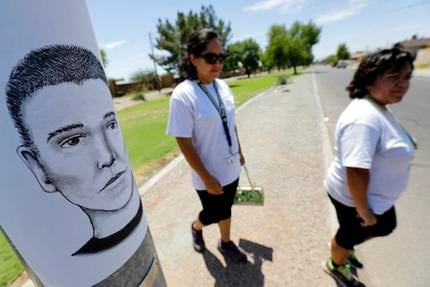 In this July 27, 2016, file photo, Phoenix neighborhood patrol officers Maribel Diaz Lopez, left, and Mario Ocampo walk a Maryvale neighborhood street in Phoenix, Ariz., to hand out an artist rendering of a suspected serial killer.