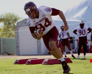 ASU football player Christian Hill runs the ball during a practice in Tempe. (Source: Chelsey Ballarte/Cronkite News)