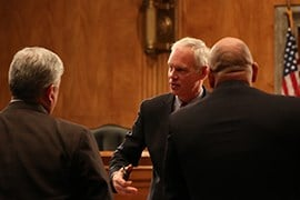 Sen. Ron Johnson, R-Wisconsin, speaks with union officials Anthony Reardon, left, and Brandon Judd after a Senate committee hearing during which they questioned the government's ability to quickly hire thousands of border and immigration officers.