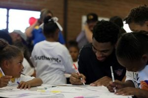 Suns forward Alan Williams drawing with kids at the newly renovated learning room of the Eastlake Community Center on Apr. 6 2017 in Phoenix. (Photo by Adonis Dees/Cronkite News)