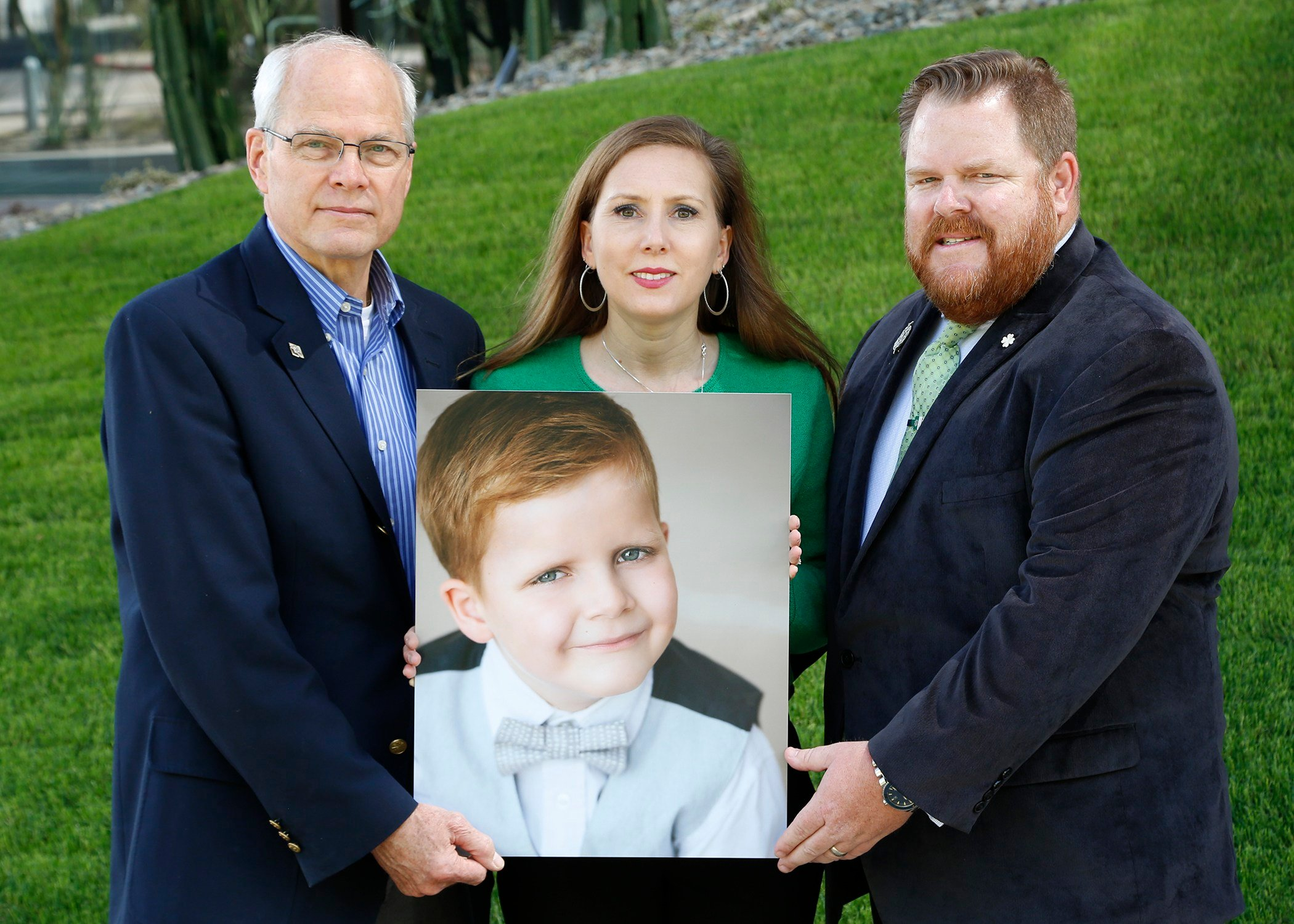TGen Dep. Director Michael Berens with Shawnee and Shane Doherty holding Hollis' photo. (Source: Hope Through Hollis at TGen)