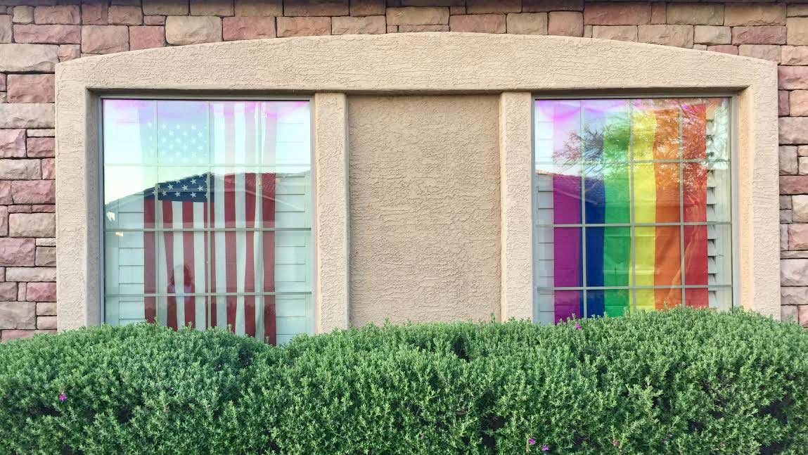 "The American and rainbow flags hang side by side inside the garage windows of Bonnie Daly's Cave Creek home. Her homeowner's association has asked she and her neighbor to remove ""unsightly items"" from public view. (Source: Mija Maslar/Cronkite News)"