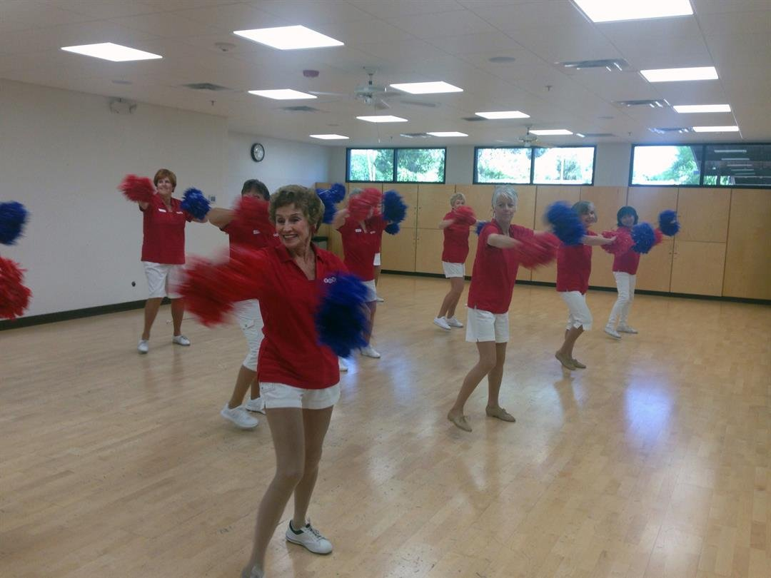 Ginger Price, in the foreground, waves her poms during a Sun City Poms dance rehearsal. (Photo by Saundra Wison/Cronkite News)
