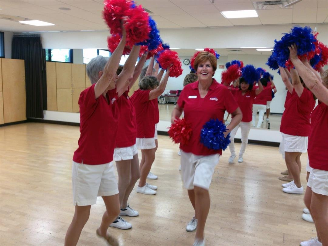 Greta Paulsen, director of the Sun City Poms, dances through a line of teammates during rehearsal. (Photo by Saundra Wilson/Cronkite News)