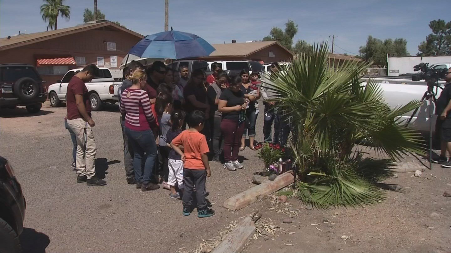 Neighbors and family pray at the scene of the shooting