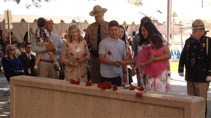 Family members of fallen DPS troopers lay roses at the memorial. (Source: 3TV/CBS 5)