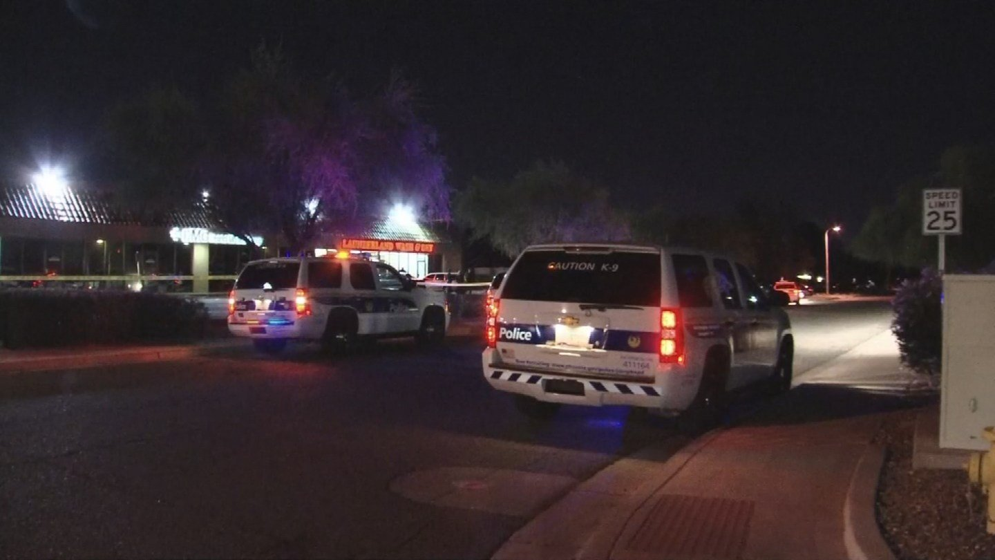 Police vehicles sit outside of the laundromat (Source: 3TV/CBS 5)