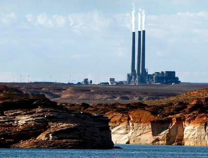 In this Sept. 4, 2011 file photo, smoke rises from the stacks of the main plant facility at the Navajo Generating Station, as seen from Lake Powell in Page, Ariz. (SOURCE: AP Photo/Ross D. Franklin)