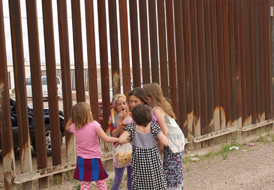 A group of young girls gathers near the border fence during an earlier Concert Without Borders. (Photo courtesy of the Bi-national Arts Institute)