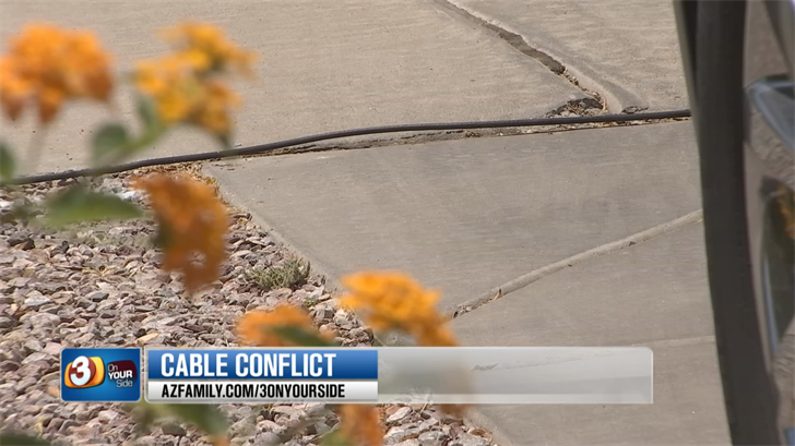 The exposed cable came out of a box found on Miller's property, traveled down sidewalks, driveways and snaked onto the property of another homeowner. (Source: 3TV/CBS 5)