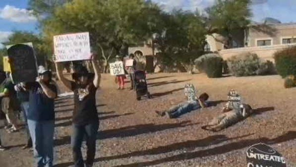 Some of them lied down on the ground, pretending to be dead, and held up a gravestone. (Source: Indivisible Southern Arizona)