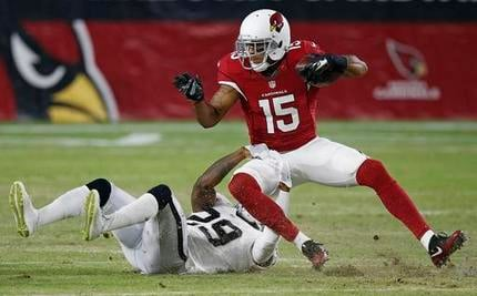Arizona Cardinals' Michael Floyd (15) gets pulled down by Oakland Raiders' David Amerson (29) during the first half of an NFL preseason football game Friday, Aug. 12, 2016, in Glendale, Ariz. (Source: AP File Photo/Ross D. Franklin)