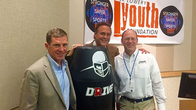 Dartmouth football coach Buddy Teevens, former NFL kicker Nick Lowery and MVP CEO John Currier, introduced the robotic MVP tackling dummy at the second annual Future of Football conference in Phoenix. (Source: Matt Faye/Cronkite News)