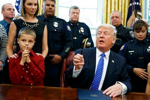 Glasser's family attended an Oval Office signing ceremony during which Trump signed a proclamation declaring Monday as Peace Officers Memorial Day. (Source: The Associated Press)