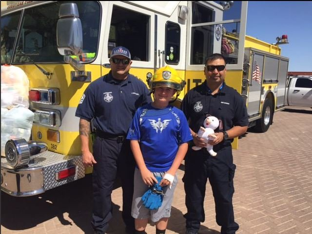 """Goodyear firefighters presented Trace with a """"fire chief challenge coin"""" for his hard work. (Source: Goodyear Fire Department)"""