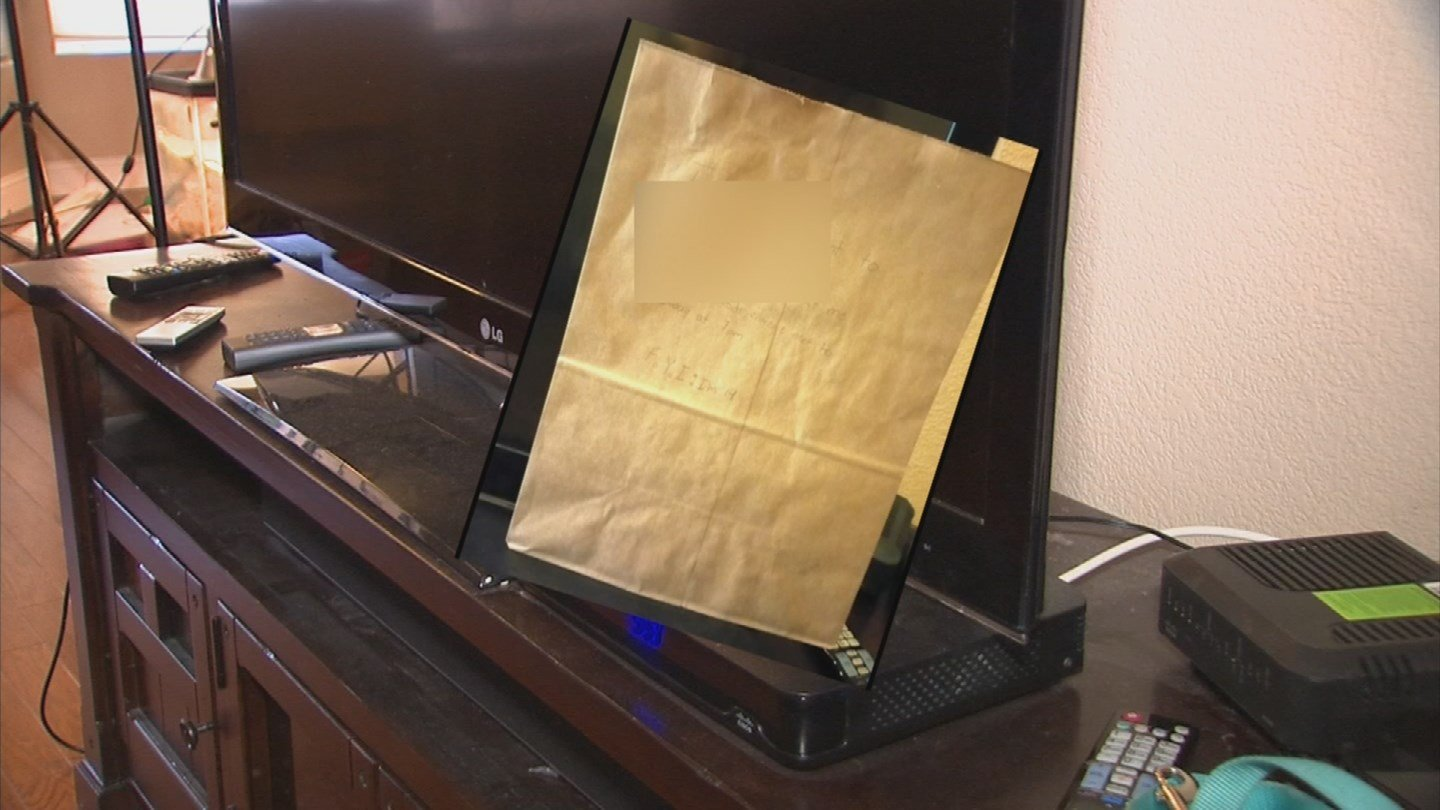 The note was handwritten on a grocery bag and placed on the woman's television. This composite image shows the note and the approximate location on the TV. (Source: 3TV/CBS 5)