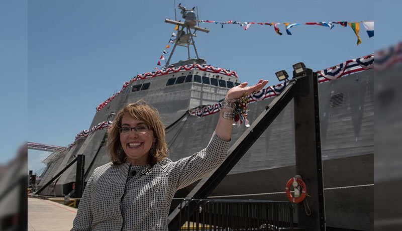 Former U.S. Rep. Gabrielle Giffords waves o a crowd in front of the littoral combat ship that carries her name. (Source: Austal USA/Released)