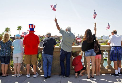People wave American flags on the Lake Havasu London Bridge to show support (Source: Associated Press)