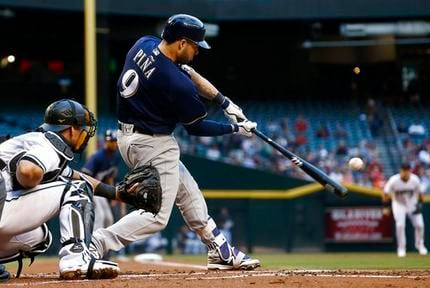Milwaukee Brewers' Manny Pina connects for a two-run double as Arizona Diamondbacks' Jeff Mathis, left, watches during the first inning of a baseball game Friday, June 9, 2017, in Phoenix. (AP Photo/Ross D. Franklin)