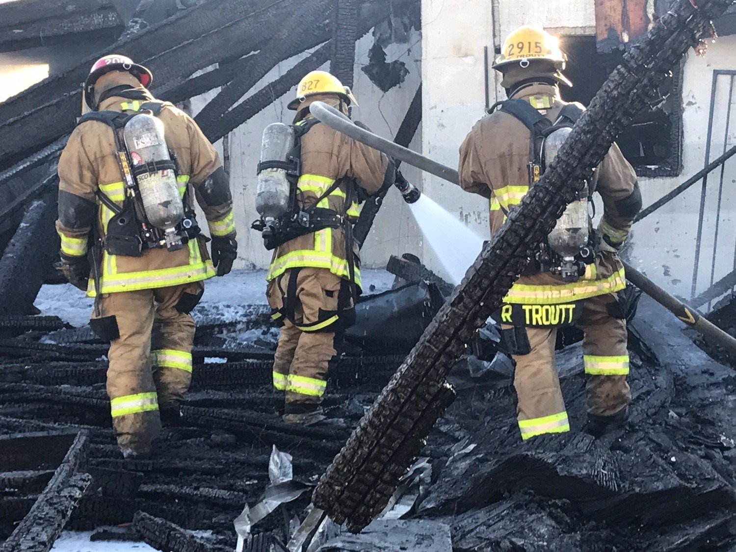 Fire fighters pick through rubble of a house fire Friday. (16 June 2017) [Source: Phoenix Fire Department]