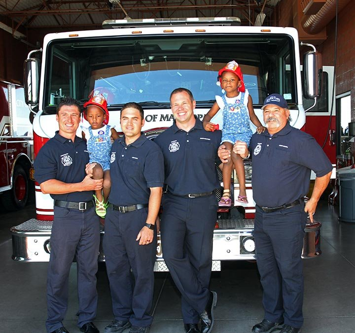 Twins with firefighters who delivered them 4 years ago. (Source: Howard WaGGner/News of Maricopa)