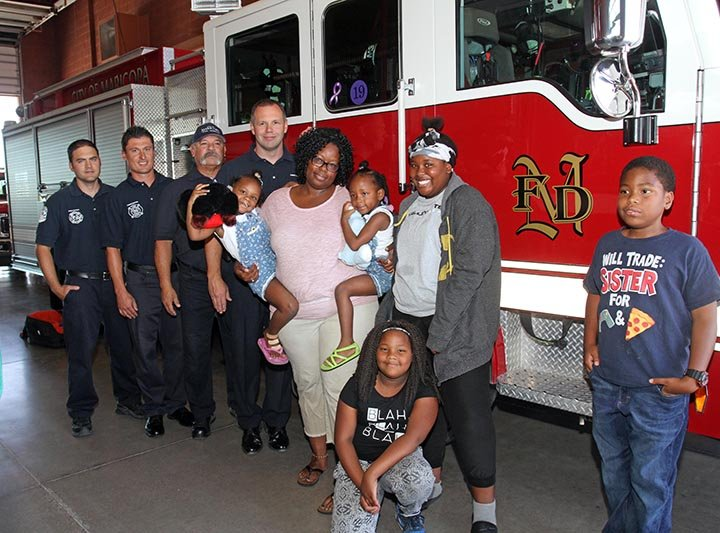 Sherese Hicks, her children and the firefighters that helped deliver her twins. (Source: Howard WaGGner/News of Maricopa)