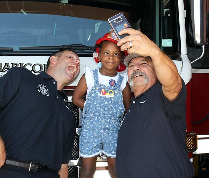 Zoe and Zoley with the firefighters that helped delivered them four years ago. (Source: Howard WaGGner/News of Maricopa)
