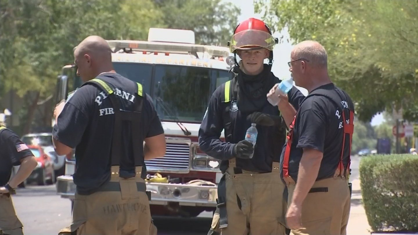 Firefighters hydrate with water at the scene of a house fire. (19 June 2017) [Source: 3TV/CBS 5 News]