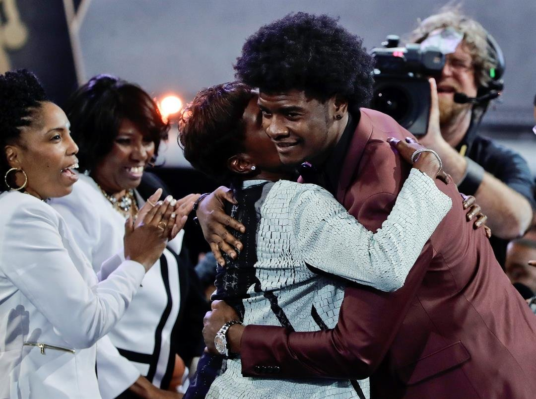 Kansas' Josh Jackson, right, hugs friends and relatives after being selected by the Phoenix Suns as the fourth pick overall during the NBA basketball draft, Thursday, June 22, 2017, in New York. (AP Photo/Frank Franklin II)