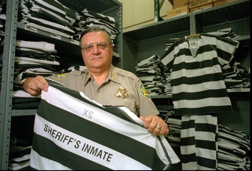 FILE-In this Thursday, April 3, 1997 file photo, Maricopa County Sheriff Joe Arpaio displays one of the new prisoner uniform tops in downtown Phoenix, Ariz. (Source: AP Photo/Scott Troyanos, File)
