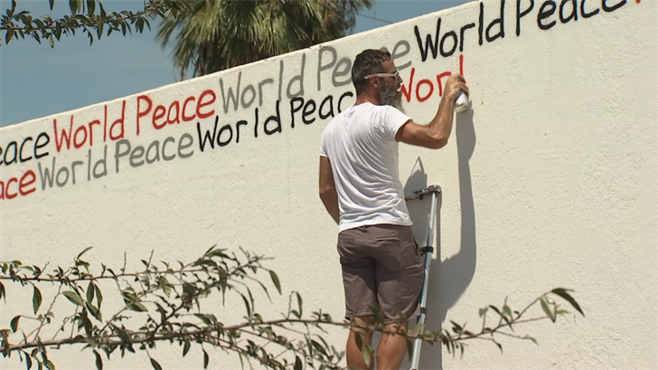 "The mural features the words ""world peace"" spray painted over and over again in different colors. (Source: 3TV/CBS 5)"