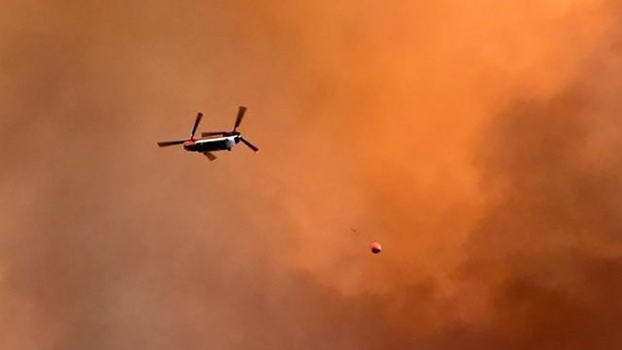 A Chinook helicopter flies over a wildfire. Photo by Christina Montiel/via U.S. Forest Service)