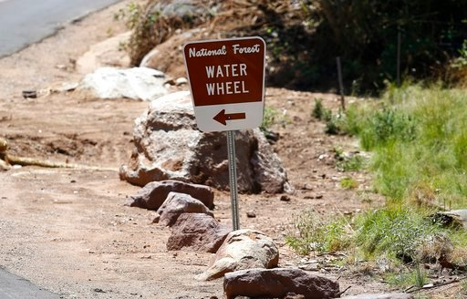 The entrance sign to the Water Wheel recreation area points the the waters where victims were caught in a flash flood along the banks of the East Verde River Monday, July 17, 2017, in Payson, Ariz. (Source: Ross D. Franklin, AP)